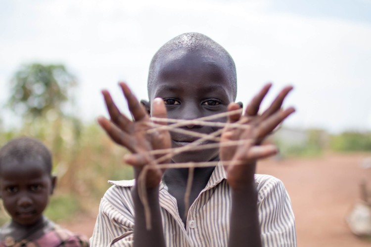 Boy Smiling While Showing Hand String Game
