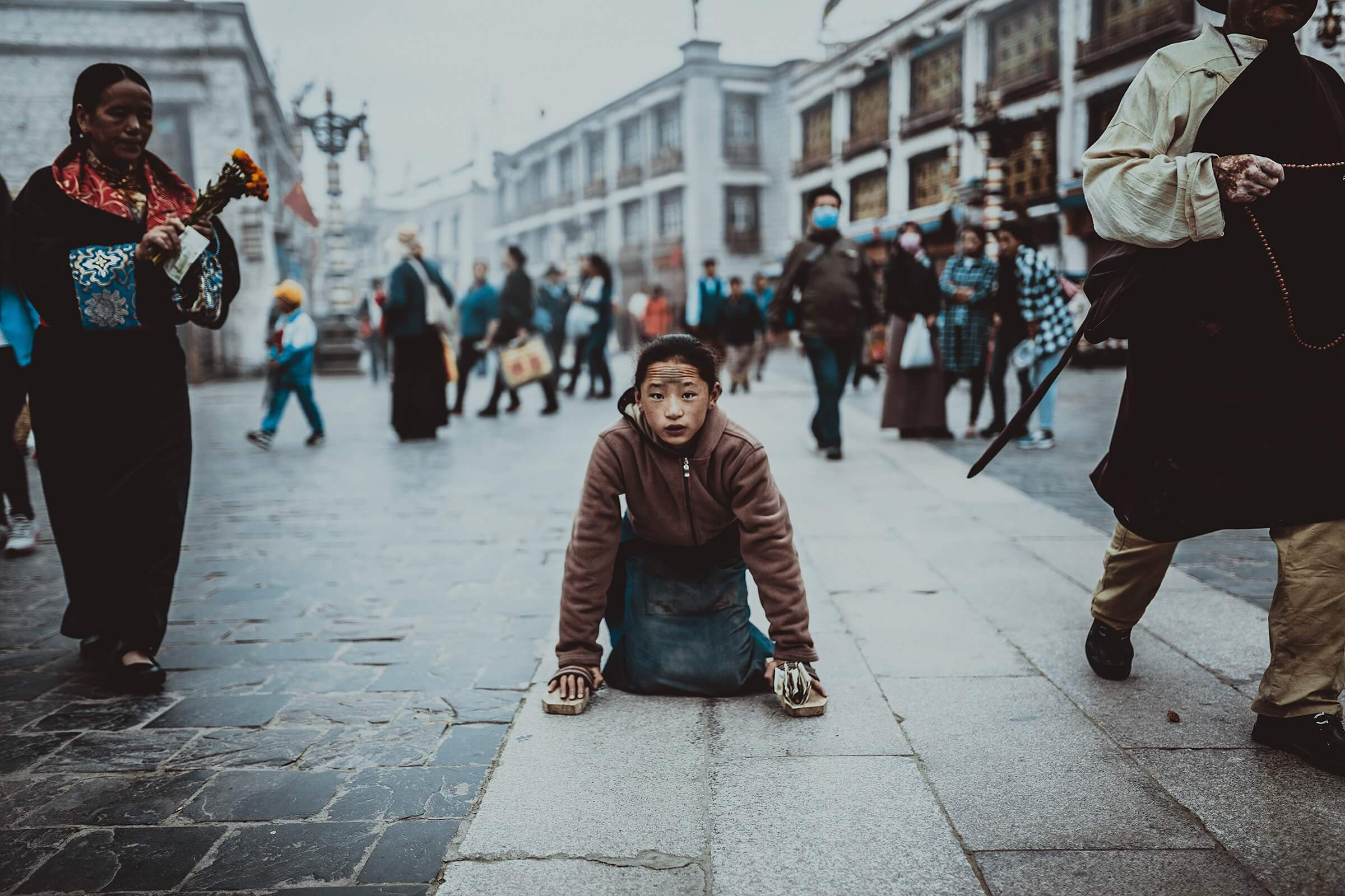 Girl Kneeling in Busy Street